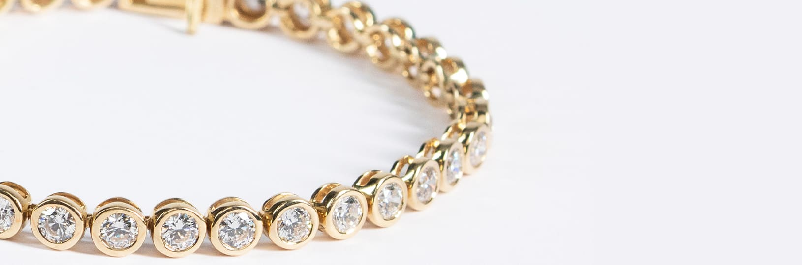 A yellow gold bracelet featuring several round cut diamonds
