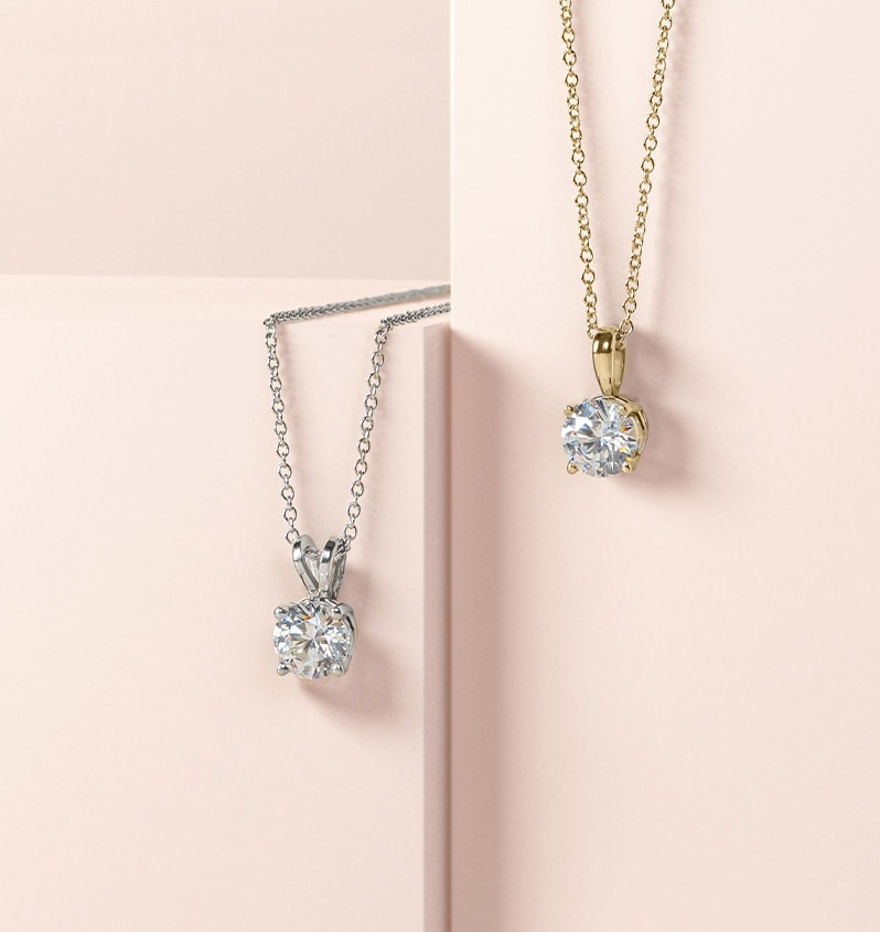 A yellow gold and a white gold pendant compared side by side
