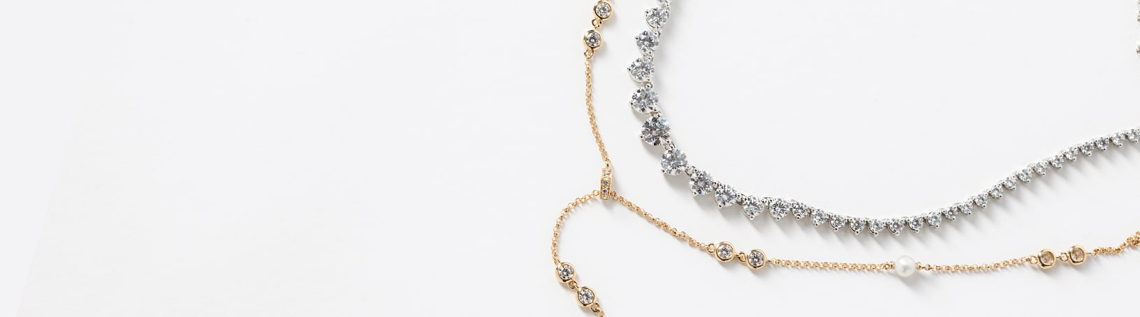 A yellow gold and a white gold necklace side by side