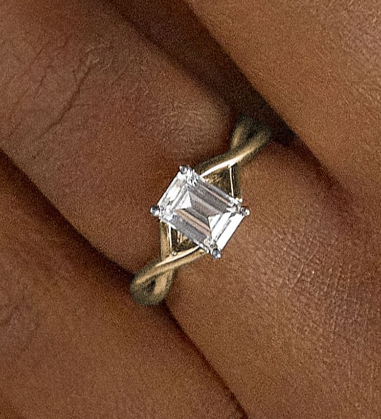 An emerald cut engagement ring with a twisted band