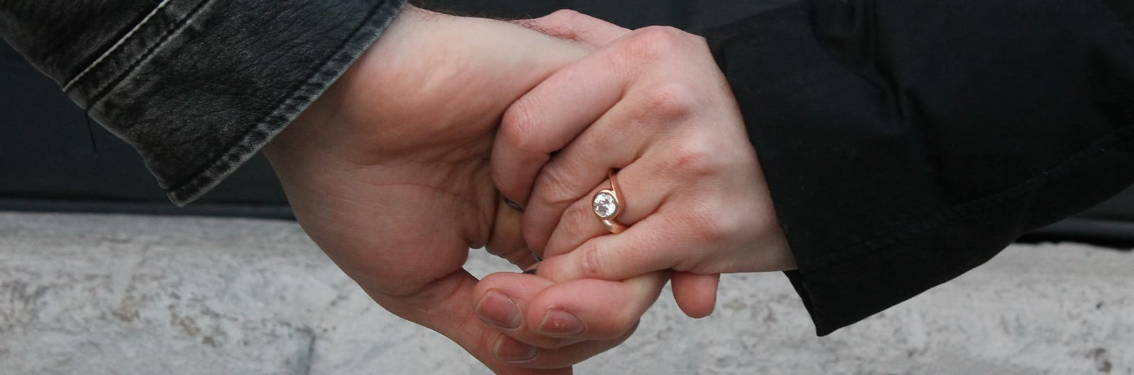 An engaged couple holding hands